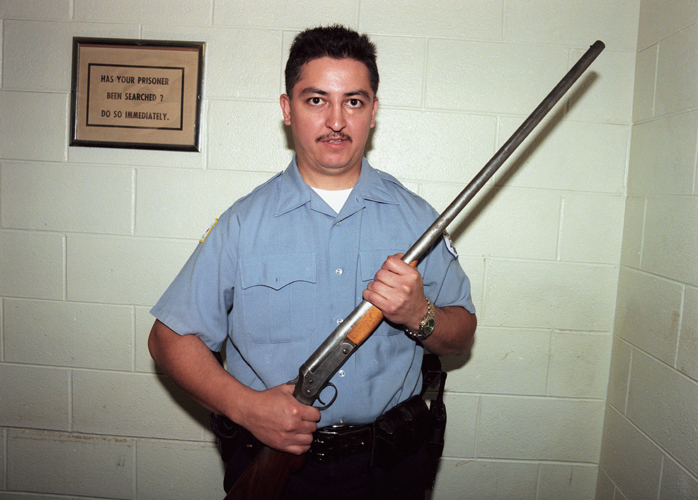 Special operations officer displays firearm confiscated from gang members in housing project, Chicago, Illinois, 2000
