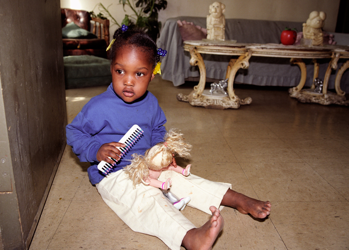 Lee Lee White with doll in doorway of grandmother's apartment in Stateway Gardens housing project before evacuation, Chicago, Illinois, 2000